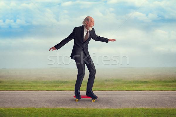 Idős férfi lovaglás gördeszka energikus élvezi Stock fotó © leeavison