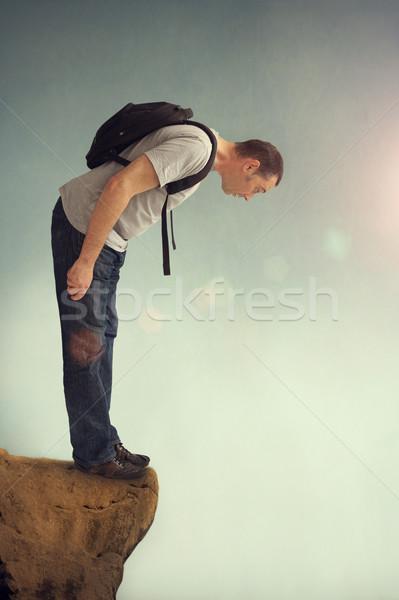 Uomo guardando verso il basso jeans sola rocce escursioni Foto d'archivio © leeavison