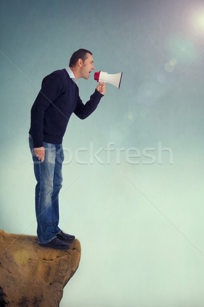 man with megaphone shouting from cliff edge Stock photo © leeavison