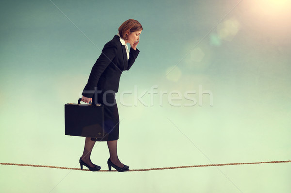 confident businesswoman walking a tightrope Stock photo © leeavison