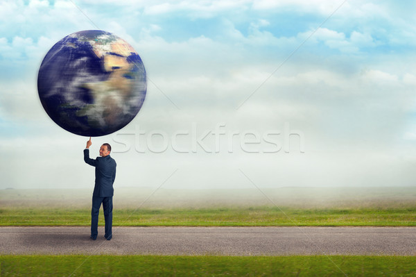 businessman holding planet earth with one finger  Stock photo © leeavison