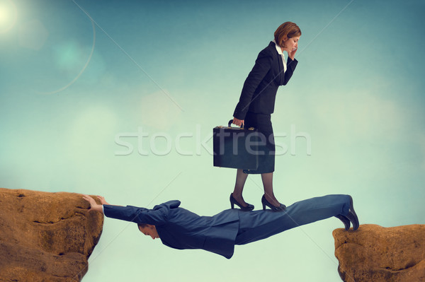 ruthless business woman walking over a vulnerable businessman Stock photo © leeavison