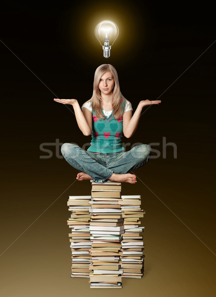 woman in lotus pose balancing on pile of books and bulb Stock photo © leedsn