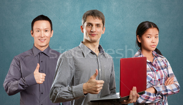 Asian team and man with laptop in his hands and woman Stock photo © leedsn