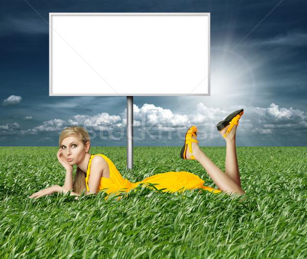 Szőke nő citromsárga ruha zöld fű óriásplakát kék Stock fotó © leedsn