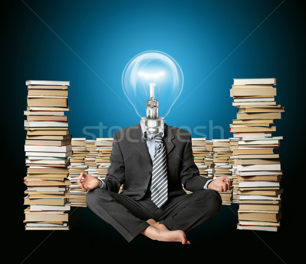 Stock photo: businessman in lotus pose and lamp-head with many books near
