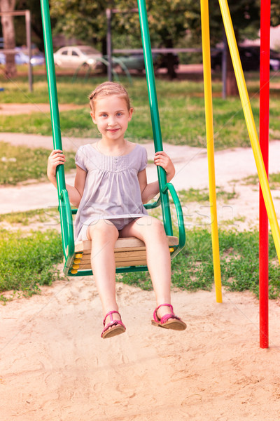 Beautiful little girl on a swings outdoor in the playground  Stock photo © Len44ik