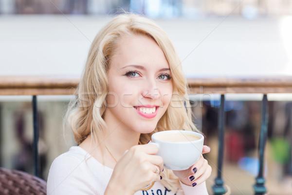 Beautiful young girl drinking coffe in a restaurant.  Stock photo © Len44ik