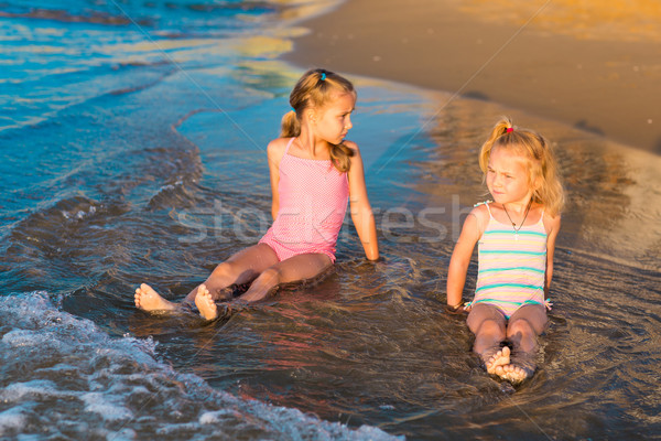 Two adorable kids playing in the sea on a beach Stock photo © Len44ik