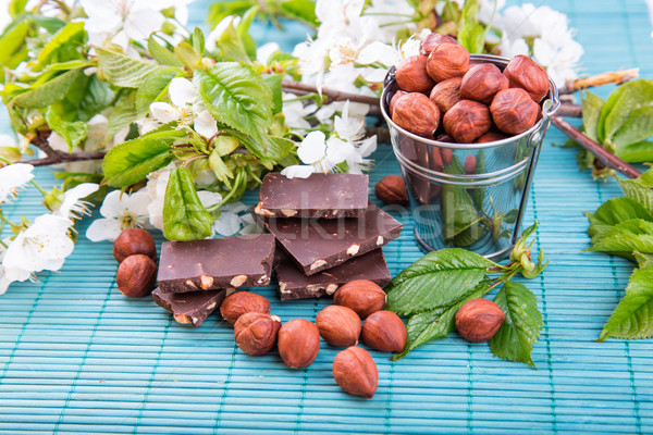 Stock photo: Hazelnuts in a backet with pieces of chocolate with nuts