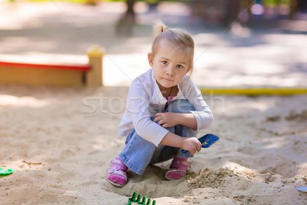 Boldog kislány játszik baba zöld homok Stock fotó © Len44ik