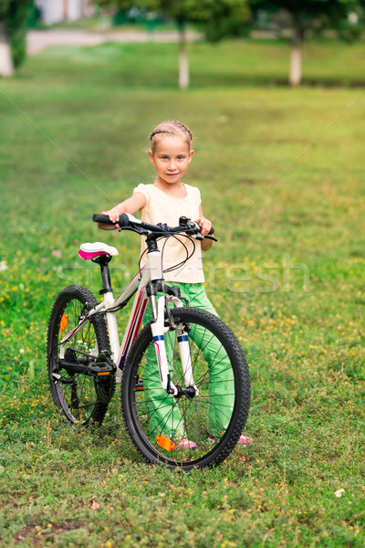 Stock photo: Little girl riding a  bicycle