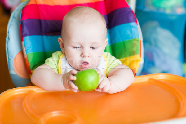 Stock photo: Adorable baby eating apple in high chair