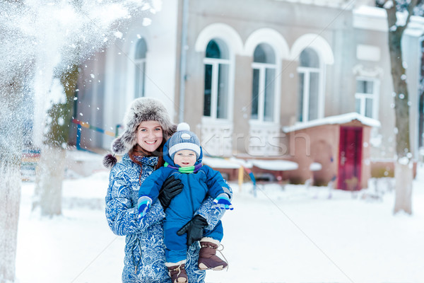 Happy mother and baby playing on snow Stock photo © Len44ik