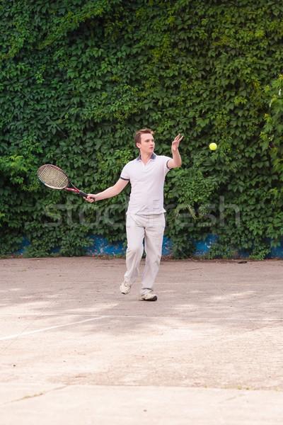 Ekspresyjny młody człowiek gry tenis zewnątrz charakter Zdjęcia stock © Len44ik