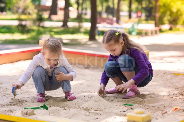 Happy little girls playing in a sendbox Stock photo © Len44ik