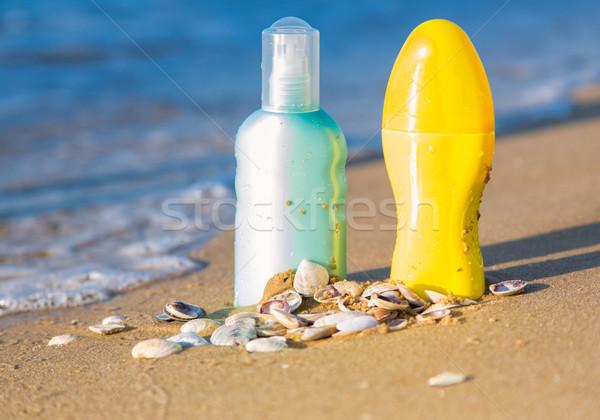 Sun protection creams on a seashore, sandy beach Stock photo © Len44ik