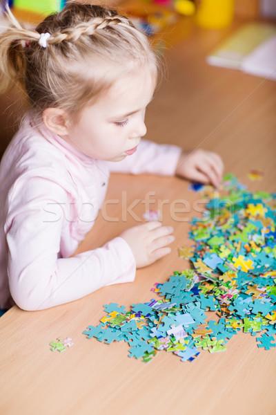 Cute little girl solving puzzles Stock photo © Len44ik