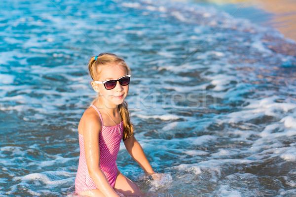 Adorable little girl playing in the sea on a beach Stock photo © Len44ik