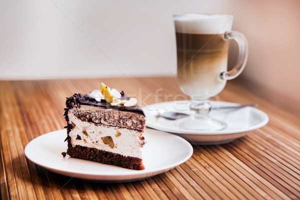 A piece of chocolate cake, coffee in the background Stock photo © Len44ik