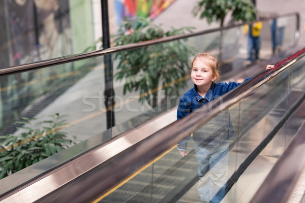 Cute little child in shopping center standing on moving escalator Stock photo © Len44ik
