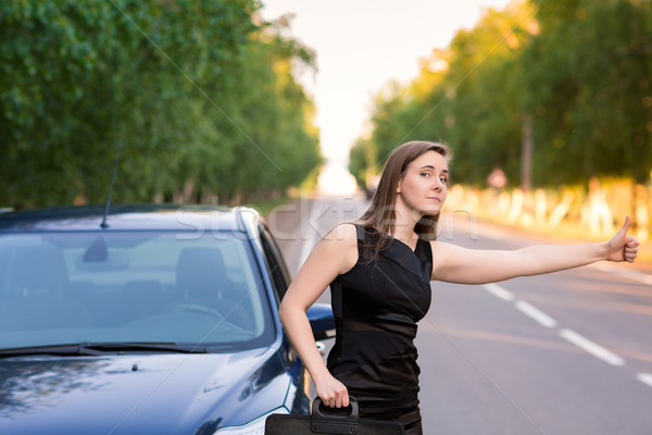 Beautiful businesswoman near her car trying to stop another car Stock photo © Len44ik