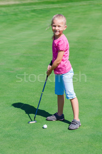 Cute little girl playing golf on a field Stock photo © Len44ik