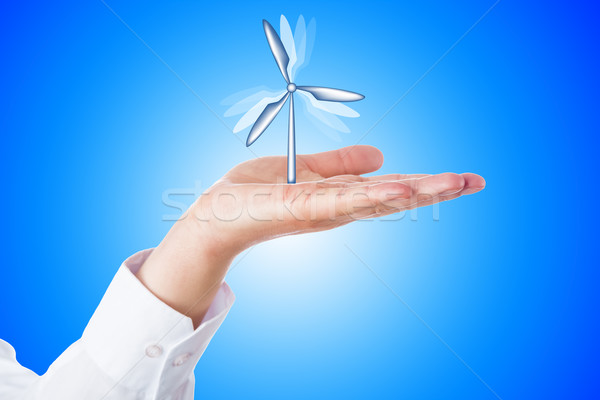 Wind Turbine Turning In A Palm On Blue Background Stock photo © leowolfert