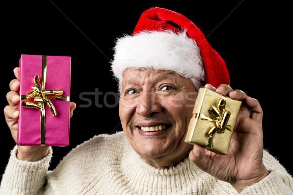 Happy Male Senior Showing Two Wrapped Presents Stock photo © leowolfert