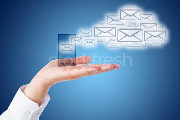 Email Cloud Leaving Smart Phone Over Blue Ground Stock photo © leowolfert