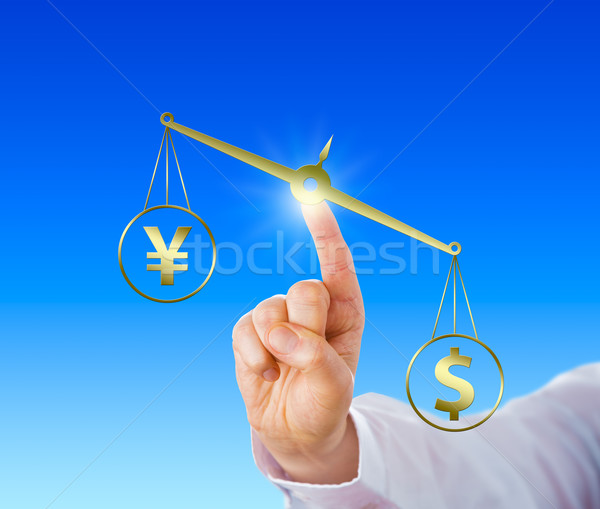 Dollar Outweighing The Yen On A Golden Balance Stock photo © leowolfert