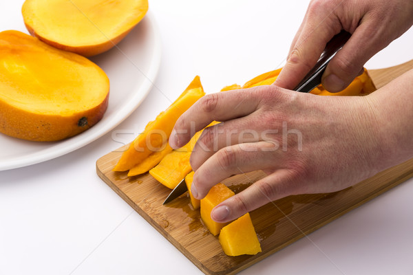 Mango Wedges Being Diced On A Wooden Cutting Board Stock photo © leowolfert