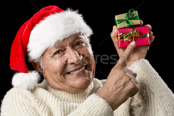 Smiling Senior Pointing At Two Wrapped Xmas Gifts Stock photo © leowolfert
