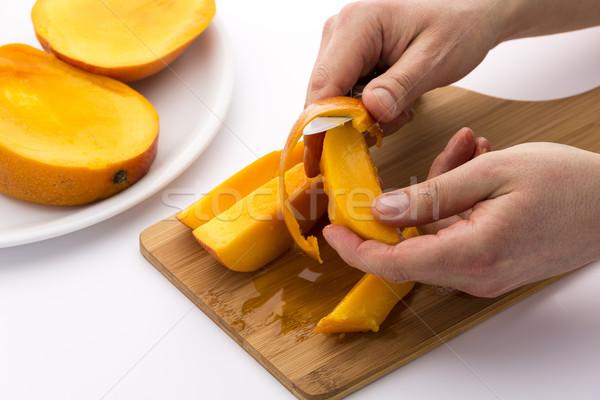 Hands Separating Mango Fruit Flesh From Its Skin Stock photo © leowolfert