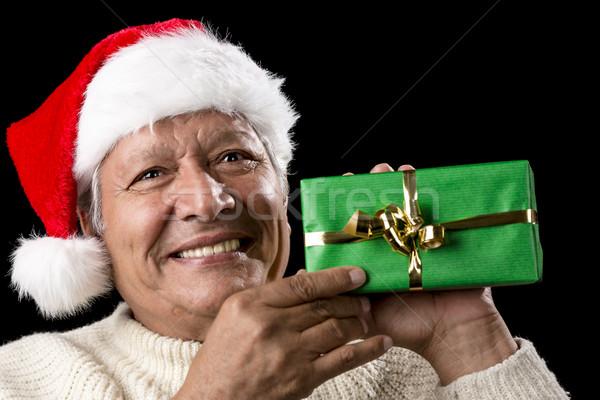 Elderly Man with Santa Cap And Green Wrapped Gift Stock photo © leowolfert