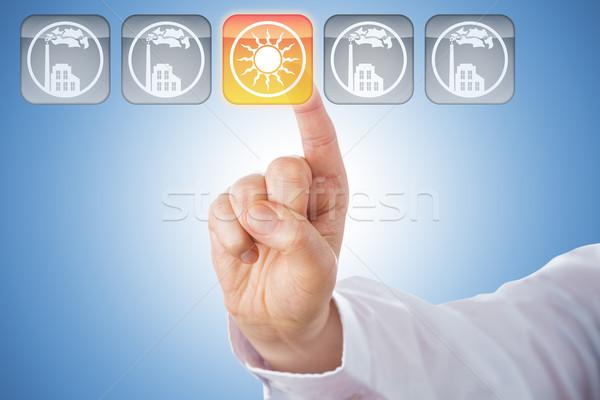 Finger Activating Yellow Solar Energy Icon On Blue Stock photo © leowolfert