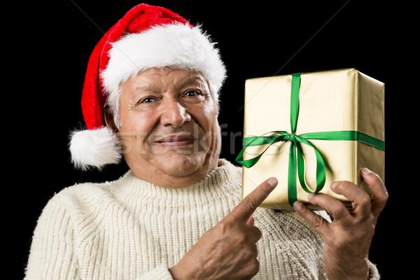 Male Senior With Santa Cap Pointing At Golden Gift Stock photo © leowolfert