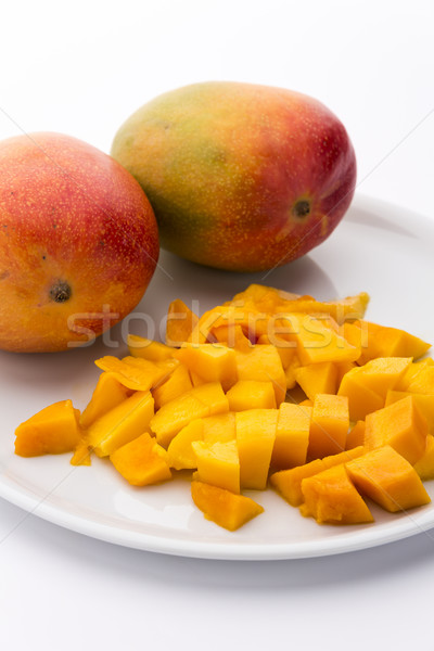 Mango Cubes And Two Whole Mangos On A White Plate Stock photo © leowolfert