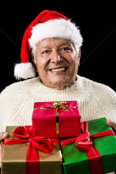 Aged Man Offering Three Wrapped Christmas Presents Stock photo © leowolfert