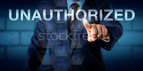 Manager Touching The Word UNAUTHORIZED Onscreen Stock photo © leowolfert