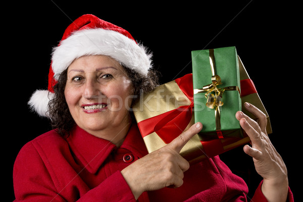 Senior Lady with Santa Cap Points at Wrapped Gifts