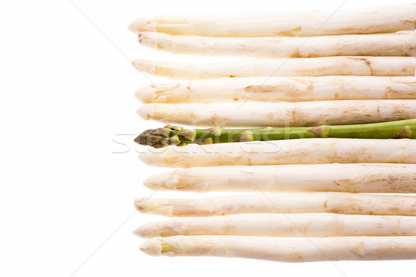 Green Asparagus Amidst Ten White Asparagus Spears Stock photo © leowolfert