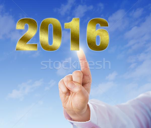 Index Finger Touching A Golden New Year 2016 Stock photo © leowolfert