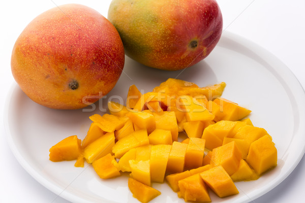 Juicy Mango Dice And Two Entire Mangos On A Plate Stock photo © leowolfert