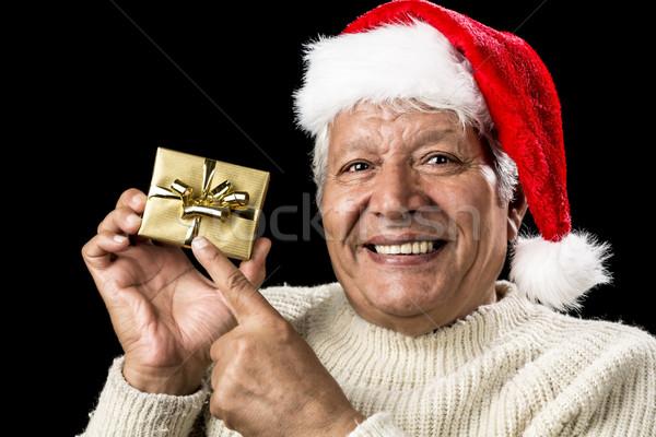 Joyful Old Man Gesturing At Wrapped Golden Gift Stock photo © leowolfert