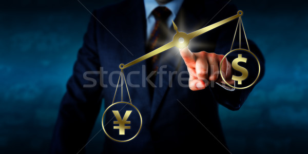 Yuan Outweighing The Dollar On A Golden Balance Stock photo © leowolfert