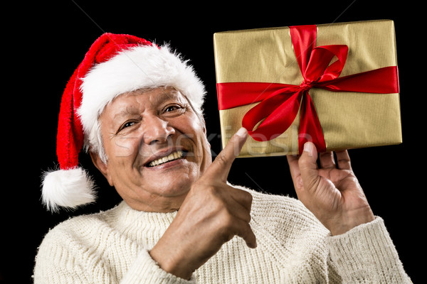 Avid Aged Man Pointing At Golden Wrapped Present Stock photo © leowolfert