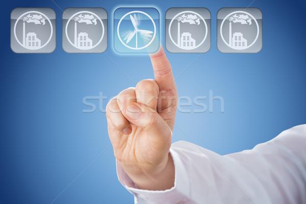 Finger Pushing Wind Power Button Over Blue Ground Stock photo © leowolfert