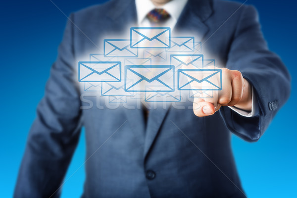 Business Man Touching A Cloud Of Many Email Icons Stock photo © leowolfert