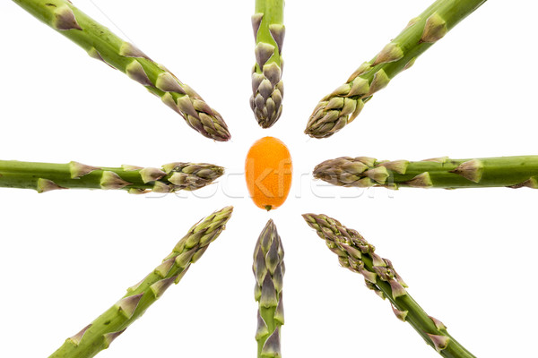 Eight Asparagus Spears Aiming at One Kumquat Stock photo © leowolfert